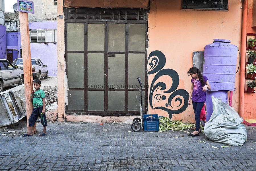 GAZA, Zaytoun: children are picking up corn peelings in the street as to keep the neighbourhood clean is part of the initiative . 15/08/15<br /> <br /> GAZA , Zaytoun :Des enfants ramassent des &eacute;pluchures de ma&iuml;s dans la rue. Garder le quartier propre fait partie de l'initiative. 15/08/15
