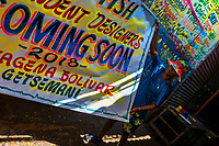 """A Colombian sign painter takes down a just-finished promotional banner in the sign painting workshop in Cartagena, Colombia, 14 April 2018. Hidden in the dark, narrow alleys of Bazurto market, a group of dozen young men gathered around José Corredor (""""Runner""""), the master painter, produce every day hundreds of hand-painted posters. Although the vast majority of the production is designed for a cheap visual promotion of popular Champeta music parties, held every weekend around the city, Runner and his apprentices also create other graphic design artworks, based on brush lettering technique. Using simple brushes and bright paints, the artisanal workshop keeps the traditional sign painting art alive."""