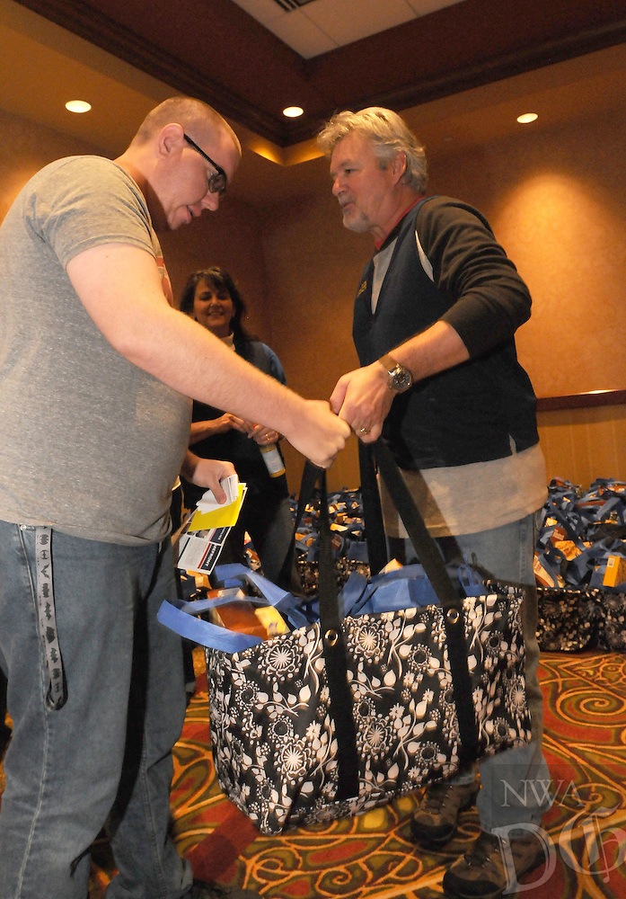 NWA Democrat-Gazette/FLIP PUTTHOFF<br /> Josh Billy (cq) (left) gets a Christmas dinner bag Saturday Dec. 12, 2015 from Bob Blumenstein. Walmart associates and volunteers distributed the bags containing all the ingredients for a Christmas dinner.