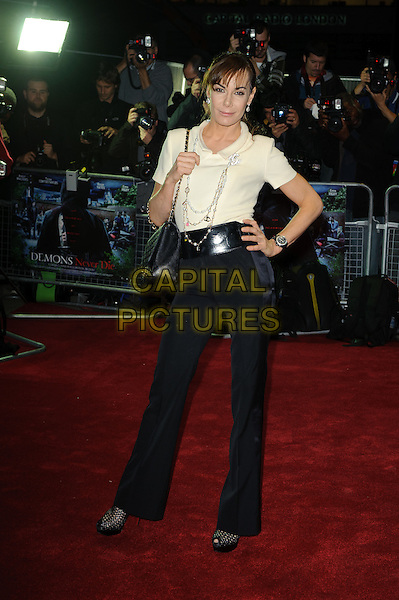 Tara Palmer Tomkinson.UK film premiere of 'Demons Never Die' held at the Odeon West End - Arrivals.London, England..October 10th, 2011.full length white top black trousers belt hand on hip tpt bag purse .CAP/CJ.©Chris Joseph/Capital Pictures.
