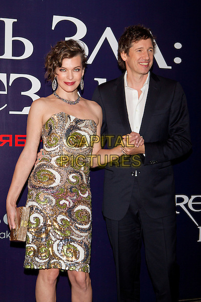 Milla Jovovich & Paul W. S. Anderson.Premiere for 'Resident Evil: Retribution', Moscow, Russia..September 6th, 2012.half 3/4 length dress gold white silver strapless sequins sequined necklace holding hand smiling married husband wife clutch bag .CAP/PER/SB.©SB/PersonaStars/CapitalPictures