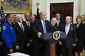 United States President Donald J. Trump, flanked by Vice-President Mike Pence (2-L), Apollo 11 astronaut Buzz Aldrin (5-L) and Commerce Secretary Wilbur Ross (R) speaks before signing an Executive Order to reestablish the National Space Council  in the Roosevelt Room of the White House in Washington, DC, on June 30, 2017.<br /> Credit: Olivier Douliery / Pool via CNP