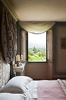The delicate net curtains hanging above the windows perfectly frame the stunning views of the surrounding hills in the bedroom