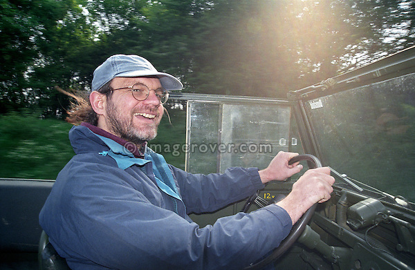 Man with cap in his thirties enjoying a drive in an open top 1950s Tempo Land Rover Series 1 86in. --- No releases available. Automotive trademarks are the property of the trademark holder, authorization may be needed for some uses.