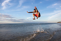 A man jumps on a Cape Cod beach.