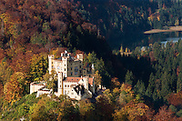 Hohenschwangau castle in with autumn colors on trees, Hohenschwangau, Bavaria, Germany