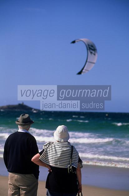 Europe/France/Bretagne/22/Côtes d'Armor/Sable-d'Or-Les-Pins: Promeneurs sur la plage de dos, face à la mer, voile de Kitesurf à l'arrière plan