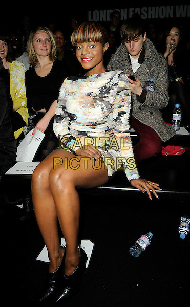KEISHA BUCHANAN.At the Eun Jeong Fashion show during London Fashion Week, BFC Show Space, Somerset House, London, England, UK, February 23rd 2010..LFW full length sitting front row  dress black pointy ankle boots long sleeved ruched print patterned pattern white blue green multi-coloured .CAP/CAN.©Can Nguyen/Capital Pictures.