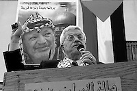 Palestinian President Mahmoud Abbas addresses supporters  in front of a poster of late Palestinian President Yasser Arafat in the West Bank town of Qalqilya December 29, 2004.  Photo by Quique Kierszenbaum