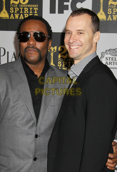 LEE DANIELS & GUEST.25th Annual Film Independent Spirit Awards - Arrivals held at the Nokia Event Deck at L.A. Live, Los Angeles, California, USA, 5th March 2010..indie half length black suit grey gray sunglasses handlebar moustache mustache smiling .CAP/ADM/MJ.©Michael Jade/AdMedia/Capital Pictures.