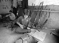 Pakistan 1986 .Darra Adamkhel is Pakistan's largest weapons bazaar and factory, renowned for its gun making expertise since the late 19th century, Darra is a sprawl of hundreds of workshops where some 3,500 gunsmiths toil on replica weapons..Factory ifle