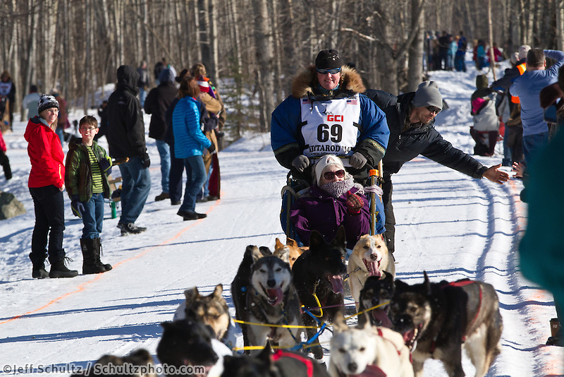 Mike Santos and team run past spectators on the bike/ski trail during the Anchorage ceremonial start during the 2014 Iditarod race.<br /> Photo by Britt Coon/IditarodPhotos.com