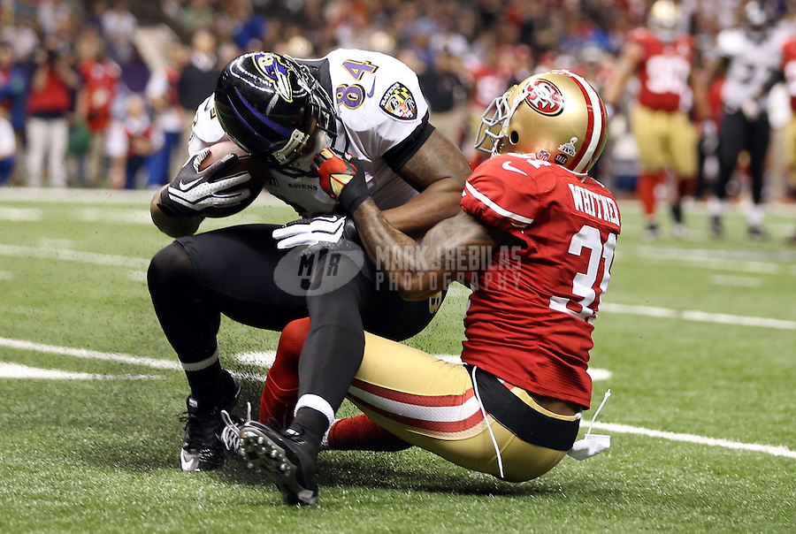 Feb 3, 2013; New Orleans, LA, USA; Baltimore Ravens tight end Ed Dickson (84) is tackled by the face mask by San Francisco 49ers strong safety Donte Whitner (31) in the second quarter in Super Bowl XLVII at the Mercedes-Benz Superdome. Mandatory Credit: Mark J. Rebilas-
