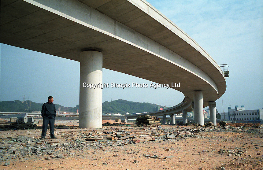 A man stands under a highway overpass in Shenzhen, Guangdong Province, China..Dec 2008