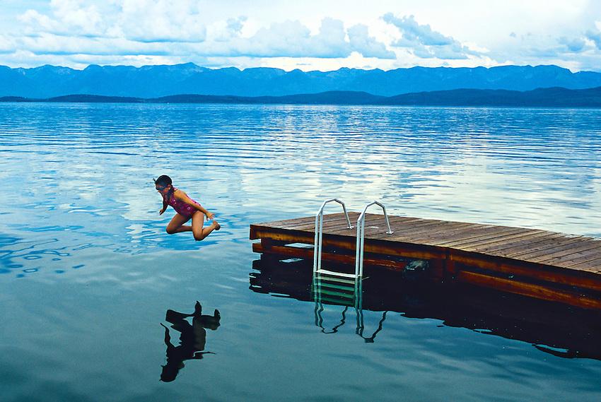 Girl jumping into Flathead Lake at Lakeside, Montana USA