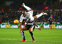 Andre Ayew of Swansea City climbs over the top of Danny Simpson of Leicester City as he wins a header during the Barclays Premier League match between Swansea City and Leicester City played at The Liberty Stadium on 5th December 2015