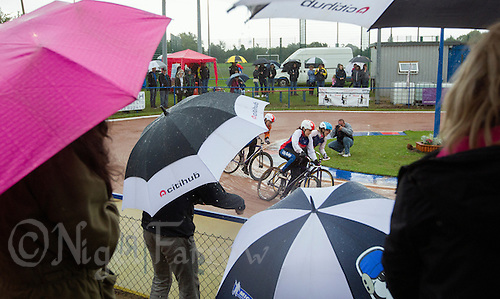 31 AUG 2015 - IPSWICH, GBR - Spectators shelter under umbrellas as they watch the women's racing at the British Cycle Speedway Championships at Whitton Sports and Community Centre in Ipswich, Suffolk, Great Britain (PHOTO COPYRIGHT © 2015 NIGEL FARROW, ALL RIGHTS RESERVED)