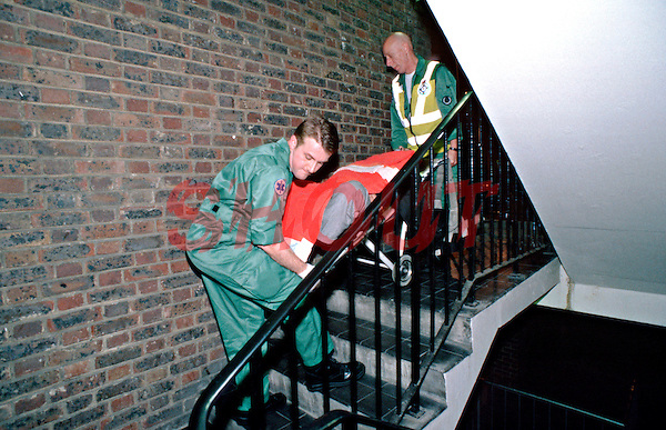 Paramedic ambulance crew carrying a patient in a wheelchair down a flight of stairs. This image may only be used to portray the subject in a positive manner..©shoutpictures.com..john@shoutpictures.com
