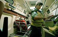 Paramedic ambulance crew attending to the victim of a heart attack in the back of an ambulance. They have the patient on oxygen and are preparing to link up an ecg machine to monitor his heart rate.