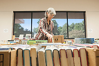 STAFF PHOTO ANTHONY REYES &bull; @NWATONYR<br /> Claudia Driver, reference coordinator for the Springdale Public Library, sorts and stacks books Monday, Sept. 22, 2014 for the Springdale Public Library's annual book sale. The sale will be Wednesday through Saturday during regular library hours. All money from the event will benefit the library and various library programs.