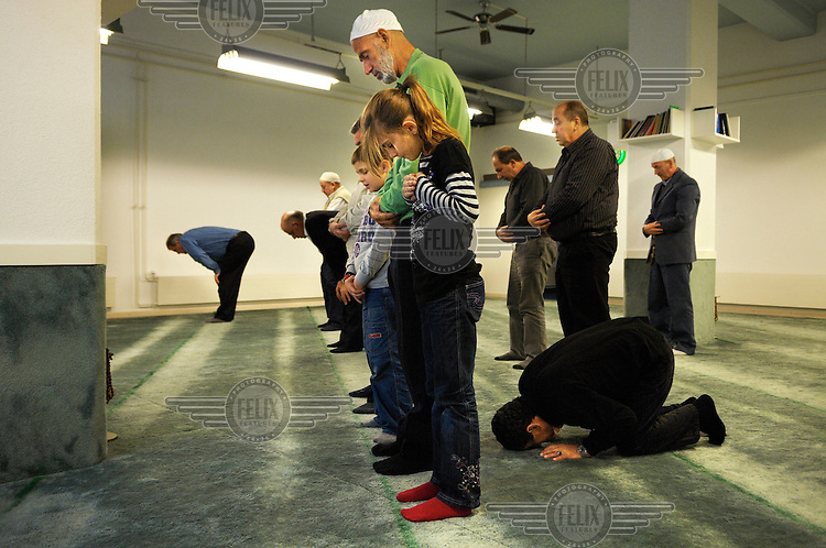 Predominantly Albanian Macedonian muslims, including a young girl, praying in the room that serves as a prayer hall and makeshift mosque on an industrial estate in the town of Wil. Their community's project to build a cultural centre including a minaret was one of the two propositions that sparked a controversial anti-minaret campaign that led to a referendum banning minarets in Switzerland.