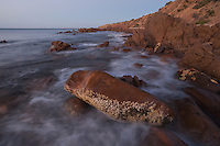 Dusk at Hallett Cove, and the waves break white against the rocky shore.