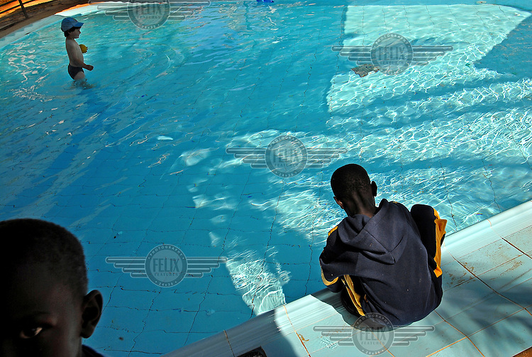 Sudanese children and an Israeli child enjoy the pool in a hotel. The hotel was financed by the Israeli government as a temporary solution, after immigrants had illegally crossed the Egyptian border into the country.