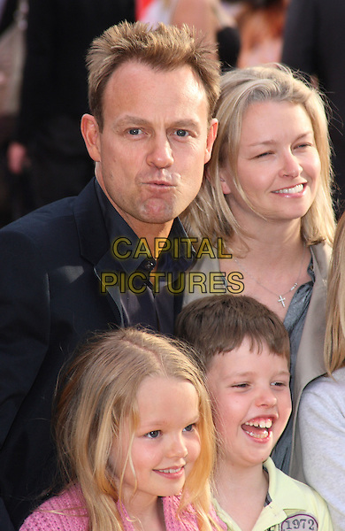 "JASON DONOVAN & FAMILY.UK Premiere of ""Hannah Montana: The Movie"" at the Odeon Leicester Square, London, England. .April 23rd 2009 .half length headshot portrait kids son daughters family father dad mother mom mum married husband wife pink jacket black funny face .CAP/JIL.©Jill Mayhew/Capital Pictures"