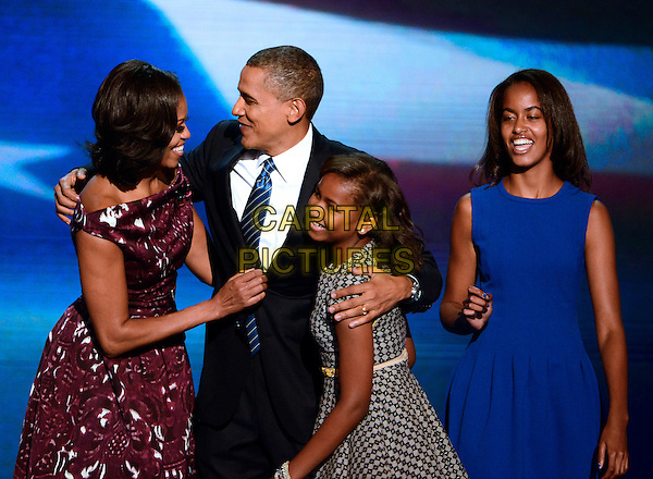 Michelle Obama, Barack Obama & daughters Malia & Sasha Obama.First family appears on stage following the acceptance speech of United States President Barack Obama .at the 2012 Democratic National Convention in Charlotte, North Carolina, USA, September 6th, 2012.  .half length  mother daughter sisters father dad husband wife purple print dress suit tie blue arms around .CAP/ADM/CNP/RS.©Ron Sachs/CNP/ADM/Capital Pictures.