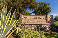 One of the entrance signs to South Gate Park, framed by maature conifers, agaves, and other plants with the park's lawns visible in the background.