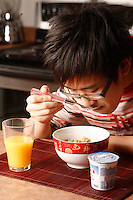 MODEL RELEASED PHOTO.<br /> A fourteen (14) year old asian male teenager, from China eat a breakfast made of cereal, yogourt and orange juice<br /> <br /> Un jeune adolescent de quatorze (14) ans d'origine Chinoise mange un dŽjeuner composŽ de cŽrŽales, yogourt et jus d'oranges. <br /> <br /> Photo : Pierre Roussel / Images Distribution