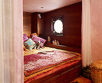 In the wood-lined bedroom a built-in bed is piled with brightly coloured scatter cushions and hung with curtains for a warm and cosy feel