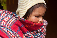 Quechua baby on the back of mom, Cusco Peru, South America