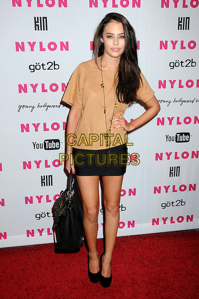 CHLOE BRIDGES .Nylon Magazine's Young Hollywood Party held at the Roosevelt Hotel's Tropicana Bar, Hollywood, California, USA..May 12th, 2010.full length hand on hip beige gold skirt black bag purse necklace brown.CAP/ADM/BP.©Byron Purvis/AdMedia/Capital Pictures.