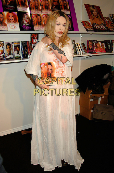 "PETE BURNS.(DEAD OR  ALIVE singer).Promoting his new book ""Freak Unique - My Story"" at the London Book Fair, Excell Centre, London, England, .March 5th 2006..full length plastic surgery lips wig long white cream dress tattoo on arm.www.capitalpictures.com.sales@capitalpictures.com.©Phil Loftus/Capital Pictures"