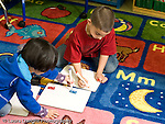 Education Elementary school Grade 1 mathematics boy and girl on floor of classroom counting domino dots for addition problems horizontal