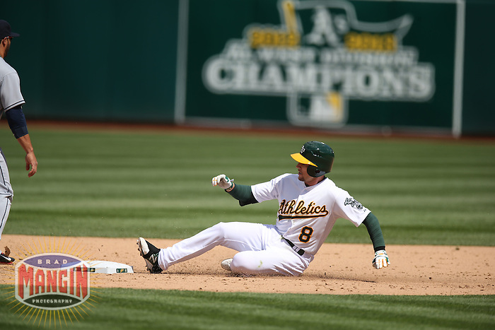 OAKLAND, CA - APRIL 2:  Jed Lowrie #8 of the Oakland Athletics slides into second base against the Cleveland Indians during the game at O.co Coliseum on Wednesday, April 2, 2014 in Oakland, California. Photo by Brad Mangin