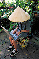 Young girl with laptop computer wearing traditional thai woven conical hat. Chiang Mai, Thailand.