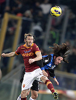 Calcio, ottavi di finale di Coppa Italia: Roma vs Atalanta. Roma, stadio Olimpico, 11 dicembre 2012..AS Roma defender Federico Balzaretti, left, and Atalanta midfielder Matias Ezequiel Schelotto, of Argentina, jump for the ball during their Italy Cup last-16 tie football match between AS Roma and Atalanta at Rome's Olympic stadium, 11 december 2012. .UPDATE IMAGES PRESS/Riccardo De Luca