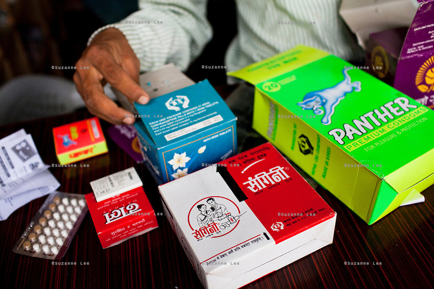 Rana Bahadur Magar, 24, holds a variety of contraceptives in his pharmacy which he bought over 2 years ago in Gangate Village, Sathakhani Bidishi, Surkhet district, Western Nepal, on 30th June 2012. Monthly, Rana Bahadur Magar sells over 300 condoms and 1700 birth control pills and does about 10 injections of 3-month-long contraceptives which he is trained to do. The nearest district hospital is an hour's drive away. In Surkhet, StC partners with Safer Society, a local NGO which advocates for child rights and against child marriage.  Photo by Suzanne Lee for Save The Children UK