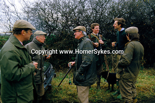 MEN HOLDING SHOTGUNS, STANDING TOGETHER TALKING & DRINKING FROM SILVER METAL CUPS, SHOOTING PHEASANT, BURLEY ON THE HILL LEICESTERSHIRE UK