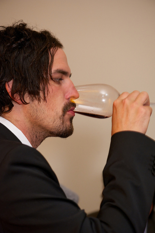 Tasting a glass of red wine.