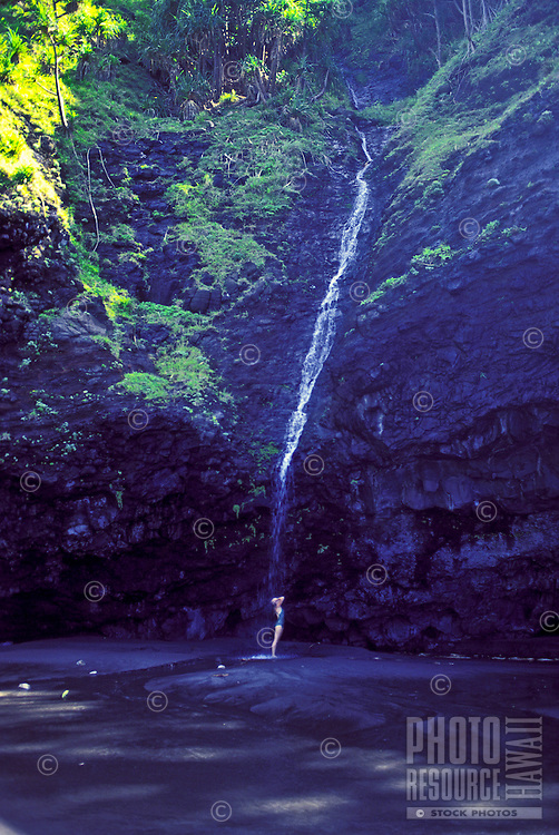 A beautiful young woman stands beneath a cascading oceanfront waterfall at the mouth of pristine Wailau Valley on the north shore of Molokai.