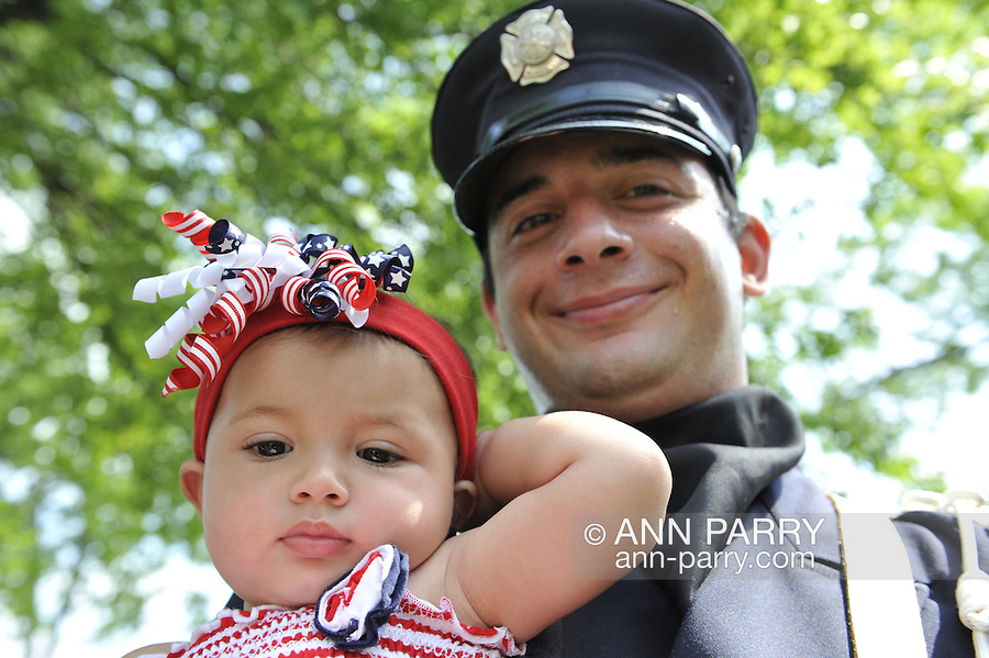 Merrick firefighters band member holds his 10-month old niece in the shade before ceremonies that followed the Merrick Memorial Day Parade on Monday, May 28, 2012, on Long Island, New York, USA. America's war heroes are honored on this National Holiday.