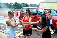Asian teen spraying white friends age 15 at car wash fund raiser.  Mound Minnesota USA