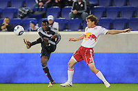 Kenny Mansally (7) of the New England Revolution crosses the ball past the defense of Chris Albright (3) of the New York Red Bulls. The New York Red Bulls defeated the New England Revolution 3-0 during a U. S. Open Cup qualifier round match at Red Bull Arena in Harrison, NJ, on May 12, 2010.