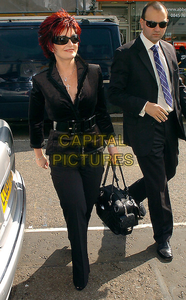 SHARON OSBOURNE.The X Factor II - press launch at The Electric Cinema, W10..August 15th, 2005.full length black trousers jacket belt sunglasses shades leather bag purse bodyguard minder.www.capitalpictures.com.sales@capitalpictures.com.©Capital Pictures