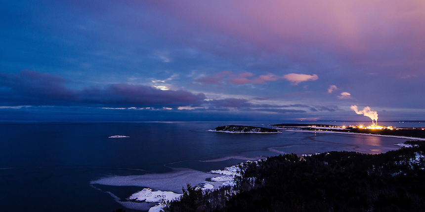 A view of Lake Superior and Marquette, MI as the full moon tries to shine through the clouds.