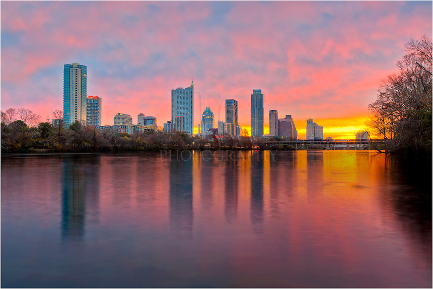 In December, the sun rises down the river of Lady Bird Lake and Zilker Park. To the north, the Austin skyline comes to life in this winter image.