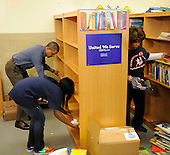 United States President Barack Obama assists in putting in book shelves as he joins volunteers in a library as they participate in a service project, at Browne Education Center, in Washington, DC, USA, on the Martin Luther King Jr national holiday, 16 January 2012. The project was in memory of the legacy of community service, promoted by the late civil rights leader, who was assassinated in 1968.  .Credit: Mike Theiler / Pool via CNP